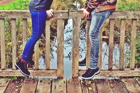 一定の距離を保ち橋の上に向き合って座り話をする男女