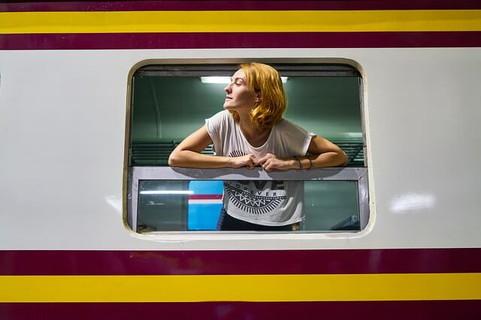 列車の窓から顔を覗かせる新しい場所へ向けて出発する女性