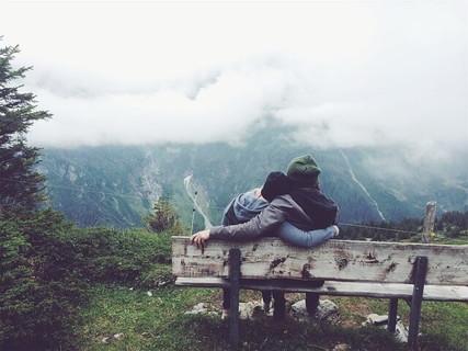 大自然の中にあるベンチに座り肩を組む旅の中で出会いカップルになった2人