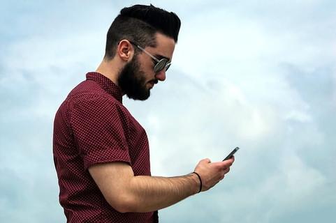 今回も空振りか…と残念そうな顔で携帯電話を覗き込むヒゲ面の男性