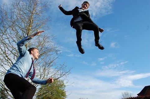トランポリンで青空に向かってジャンプする明るい男の子達