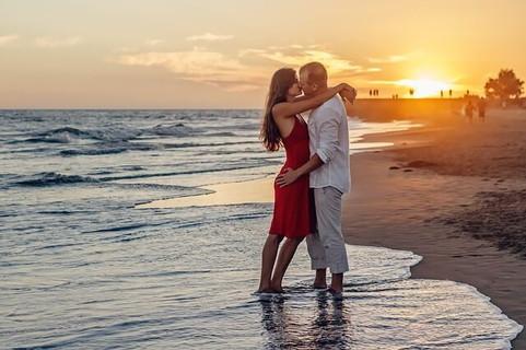 メールで関係を深めゴールインした海に沈む夕日を背にキスをするカップル