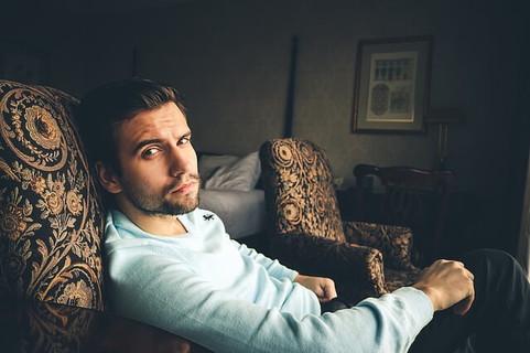 ソファに座り相手を疑うような目線を向ける男性