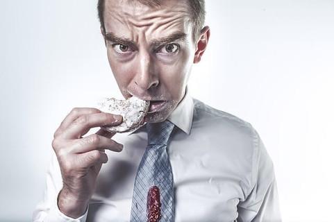 口の周りや服を砂糖だらけにしてクッキーを食べる男性