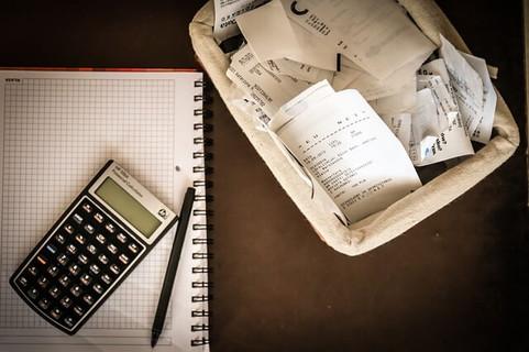 カゴいっぱいに入ったレシートとそれをすべてワリカンにするために用意された電卓とノート