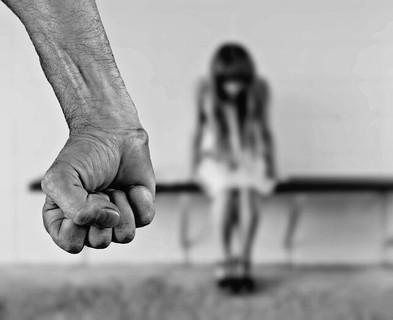 気に入らないことがあるとすぐに暴力をする男性と傷付いてうつむいて座る女性