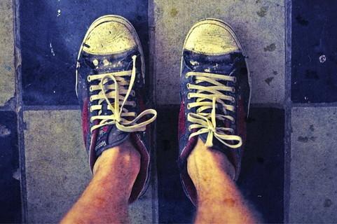 泥だらけの汚いスニーカーを履く男性の足元