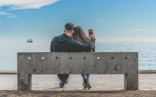 青空の下ベンチに座り幸せそうに身を寄せ合うカップル