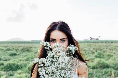 野原に立ち出会いOKのサインとしてカスミ草の花束を目の前に差し出す女性