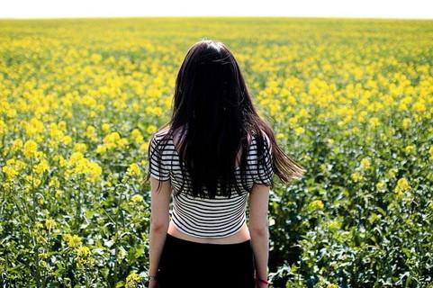 気になる人のことを考えながら菜の花畑にひとりで立つ女性