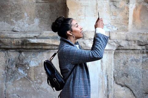 街中を歩いている時に面白いものを見つけ気になる人に写真を送る女性