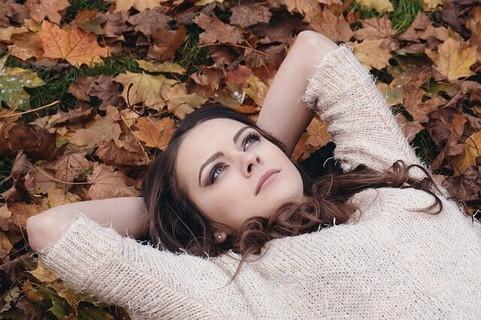 空を見上げ退屈そうに落ち葉の中に寝転がる女性