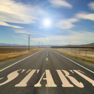 青空の中地平線に向かってまっすぐに通ったスタートが描かれた道