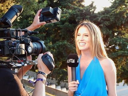 マイクを持ちカメラの前でレポートをするキラキラした笑顔の女性アナウンサー