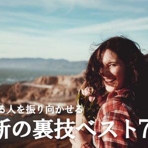 ピンク色の花束を持って笑顔で振り向く幸せそうな女性