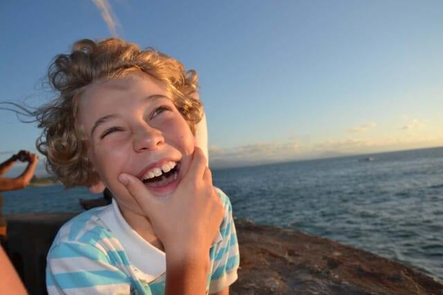青い海と空を背景にキラキラした笑顔を見せる男の子