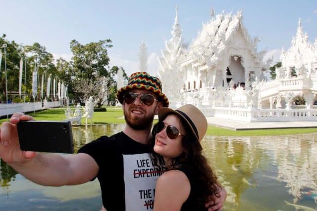 旅行先で顔を近づけて自撮りをする仲良しの男性と女性