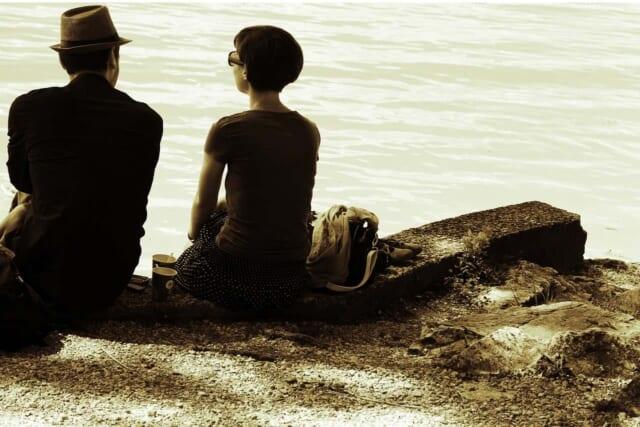 海辺に腰を下ろしコーヒーを飲みながら会話を楽しむ男性と女性