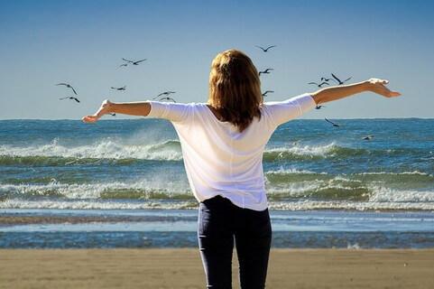 海に向かって大きく手を広げ深呼吸する女性