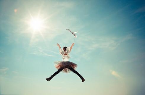 妖精の羽を背中につけて青空に向かってジャンプする女の子