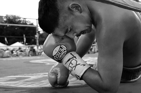 打ちのめされてリングの上で手を付くボクサー