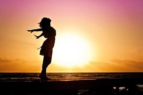 朝の光に向かって手を広げて深呼吸をする女性