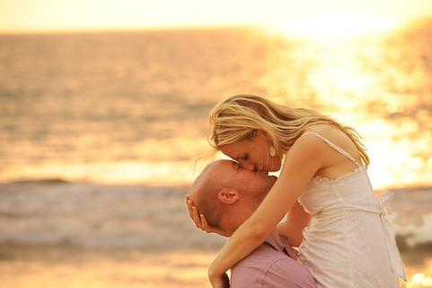 夕日が沈むビーチでキスをする幸せそうなカップル