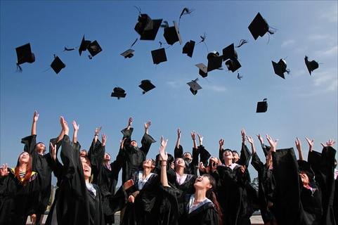 ローブを着て青空高く帽子を投げる卒業生たち