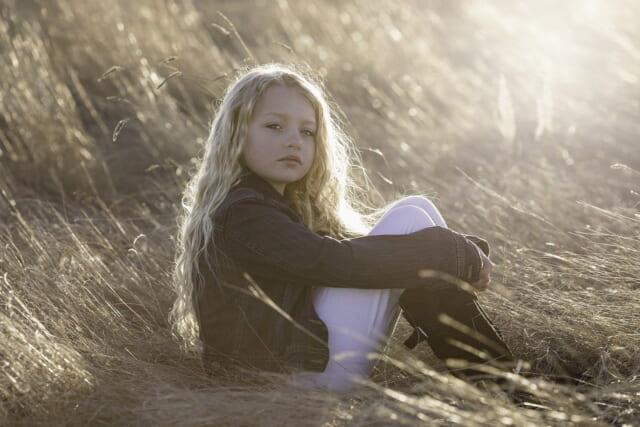 枯草の中にこちを下ろしてこちらを見る小さな子供