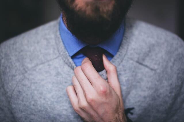 青いシャツを着てネクタイを正すアラフォー男性