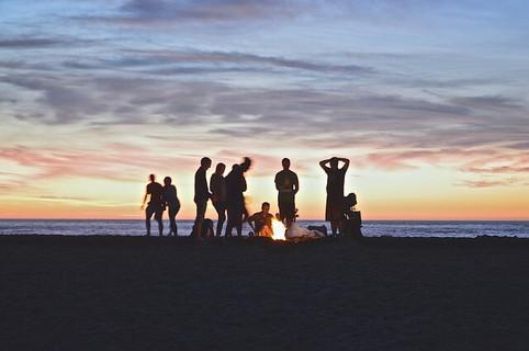 海辺の日が沈む美しい空の下で火を起こす仲間たち
