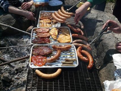 熱い網の上においしそうなお肉やソーセージを乗せて手分けして焼く人たち