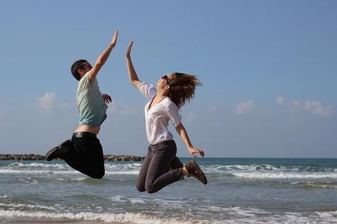 気分が盛り上がりジャンプしてハイタッチする男性と女性