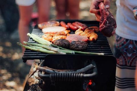 グリルの前に立ちおいしそうな野菜やお肉を焼く女性の手元