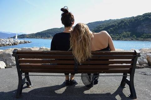 お酒に酔ってベンチで休む友達を介抱する女性