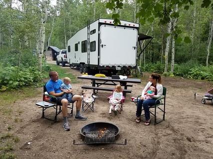キャンプ場で火を囲みゆったりとくつろぐ家族