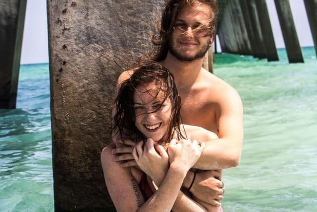 海につかりハグをする幸せそうな笑顔のカップル