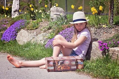 大きなトランクと一緒に道端に腰掛けてひたすら何かを待つ女の子