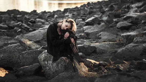 地面に座り込みものごとをマイナスに考えて首をうなだれる寂しそうな女性
