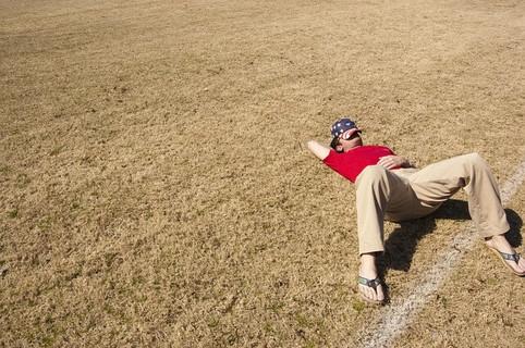 退屈そうに草むらに寝ろがり帽子を顔の上に乗せて昼寝をする男性