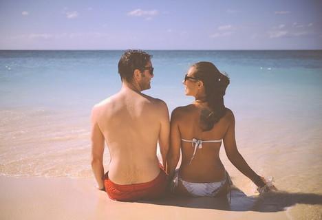 真っ白な砂浜の上に座りお互いを見つめあう水着姿のカップル
