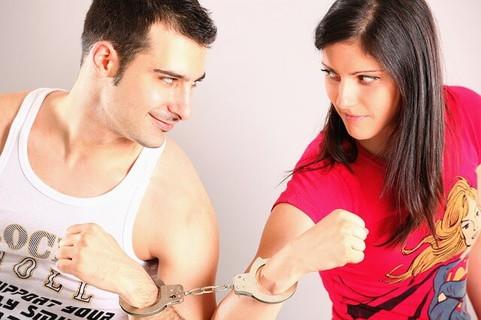 顔を見合わせるお互いの腕を手錠で繋がれたカップル