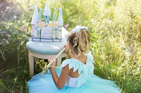 ドレスを着ておもちゃのお城を眺めるプリンセスになるのを夢見る女の子