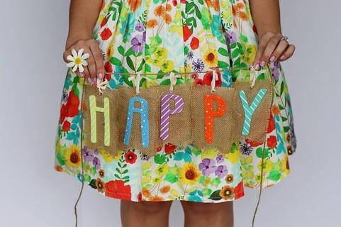 カラフルな花柄のワンピースを着てHappyの文字を持つ女の子