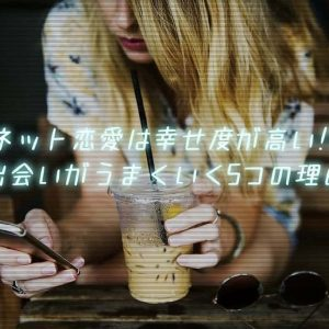 ベンチに座りカフェラテを飲みながらスマートフォンを覗き込む女性
