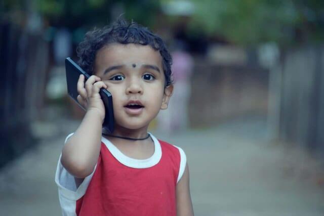 スマートフォンで楽しそうに話をする小さな男の子