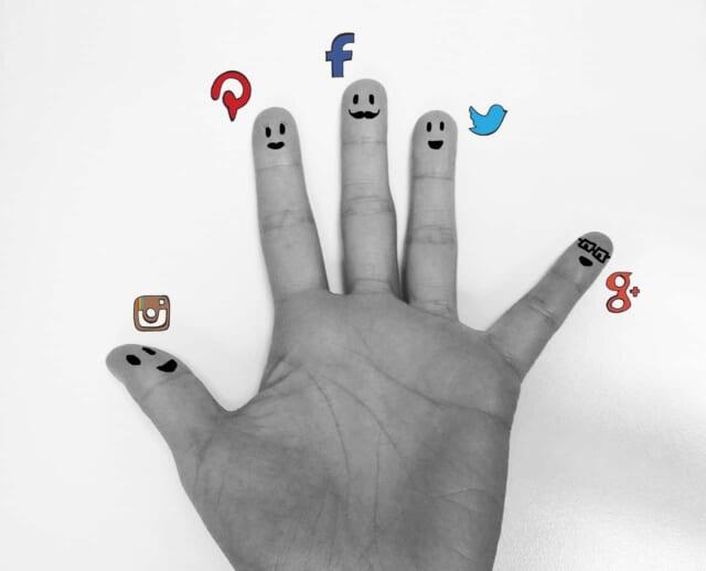 5本の指に描かれた顔とソーシャルメディアのアイコン