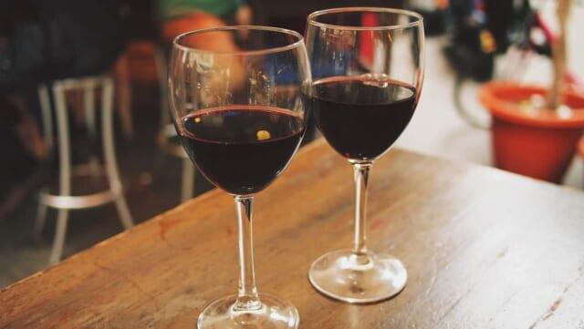 テーブルの上に並んだ赤ワインが注がれた2つのグラス
