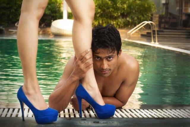 プールサイドに肘をかけ顔の見えない女性の美しい足をつかむ男性