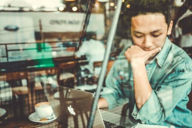 カフェでラップトップを開き肘をついて悩む男性